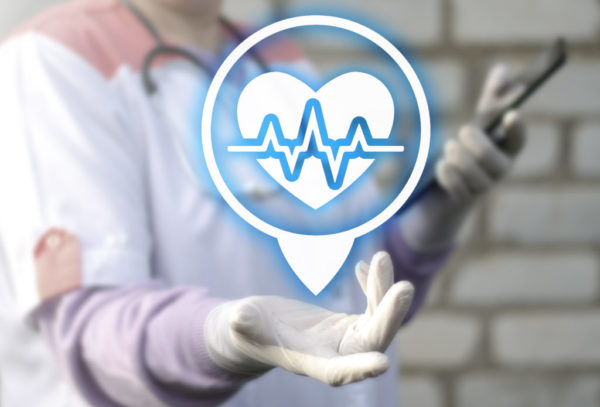 an image of a medical personnel holding tablet on its left hand and showing graphic heartbeat icon on its right hand